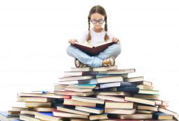niña leyendo libros en pila